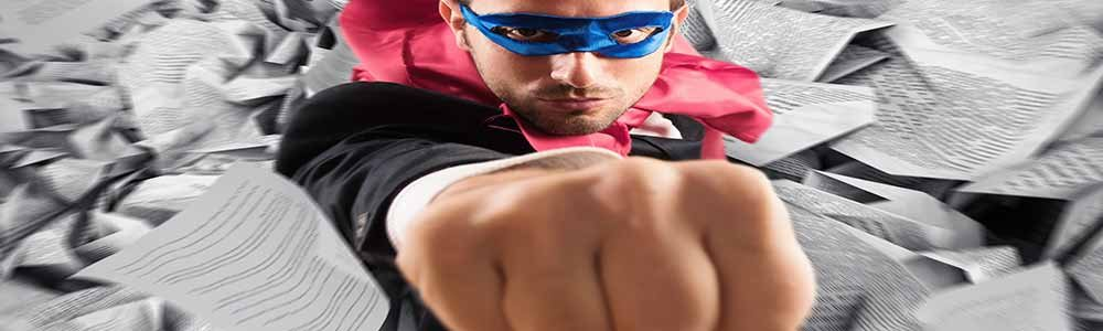Businessman in a superhero costume punching through a wall of loose documents